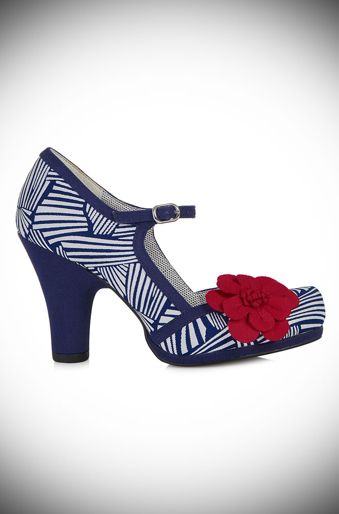 The Ruby Shoo Tanya shoes feature deco inspired faux suede jacquard details in navy and white, red floral corsages and an ankle strap.