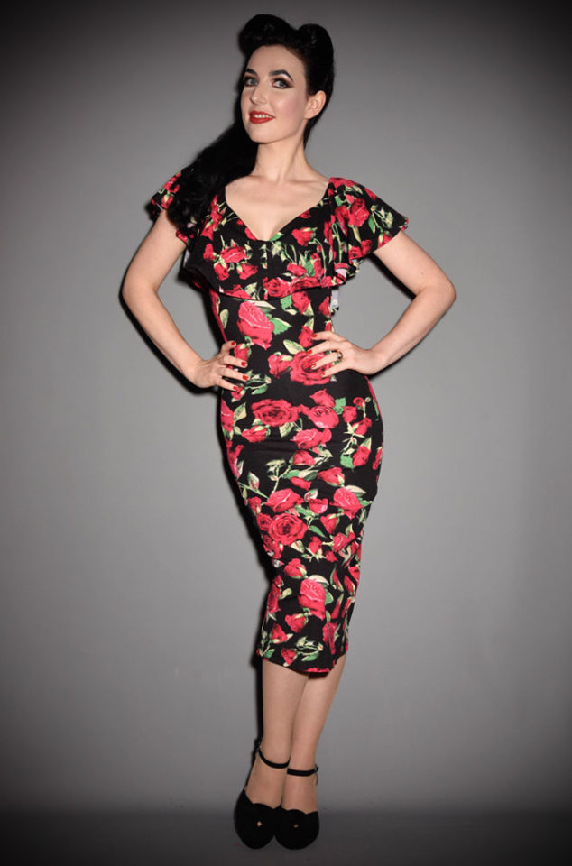 The Sophia Dress is a vintage style pencil dress by Unique Vintage at UK stockists, Deadly is the Female. Covered in red roses on a black background.