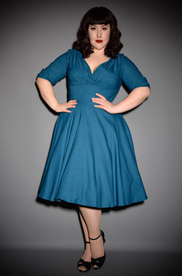 The Teal Delores dress is a striking swing dress rich in 1950s vintage appeal by Unique Vintage at UK stockists, Deadly is the Female. The Teal Delores Dress is a show stopper! Add a Petticoat and seamed stockings to turn heads in this striking swing dress, where ever you go! Perfect for pinups and retro style lovers.