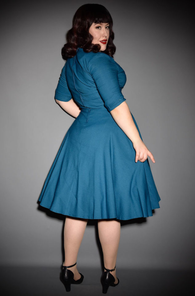 The Teal Delores dress is a striking swing dress rich in 1950s vintage appeal by Unique Vintage at UK stockists, Deadly is the Female. TheTeal Delores Dress is a show stopper! Add a Petticoat and seamed stockings to turn heads in this striking swing dress, where ever you go! Perfect for pinups and retro style lovers.