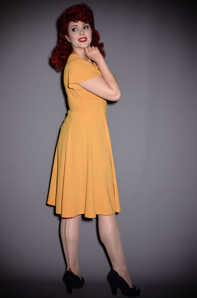 The Mustard Grable Dress has been designed to be as faithful as possible to the 1940s styles. A slimming fit around the waist withelegant shortsleeves will float you through any dance. The mustard colour is gloriously light & bright in the summer but warm enough in tone to take you through to the winter months!
