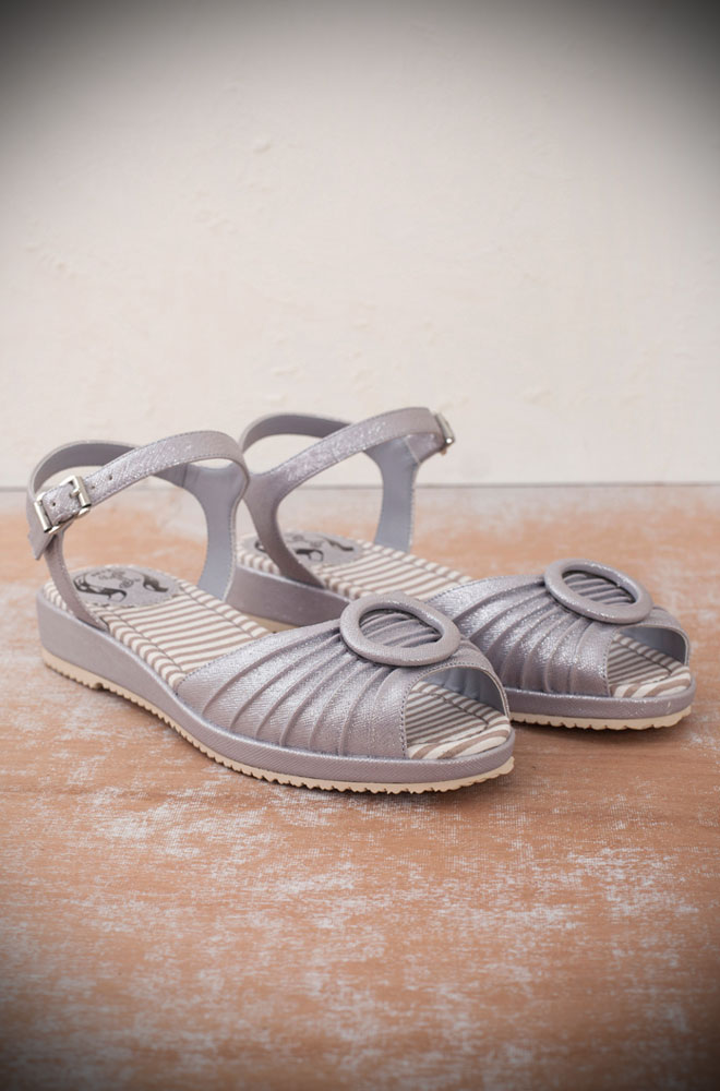 The Miss L Fire silver Adrianna sandals are 1940's style mini-wedge sandals. This casual shoe has been given a fun and glamorous edge with the striking silver sparkles. Perfect for pairing with your favourite summer dress and idea with some 50's style jeans or capris!