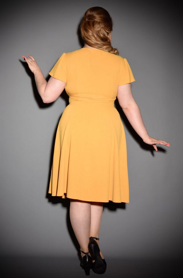 The Mustard Grable Dress has been designed to be as faithful as possible to the 1940s styles. A slimming fit around the waist with elegant short sleeves will float you through any dance. The mustard colour is gloriously light & bright in the summer but warm enough in tone to take you through to the winter months!