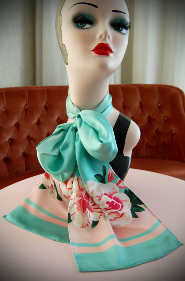 """This mint green scarf features beautiful pink roses and hibiscus and a gorgeous little """"Honeybird"""". Measuring 20cm wide by 180cm long, theHoneybird silk scarf can be worn in a number of ways. Deadly is the Female are UK stockists of Woody ellen."""