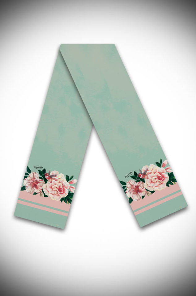 "This mint green scarf features beautiful pink roses and hibiscus and a gorgeous little ""Honeybird"". Measuring 20cm wide by 180cm long, theHoneybird silk scarf can be worn in a number of ways. Deadly is the Female are UK stockists of Woody ellen."