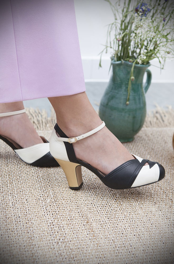 The Miss L Fire Black, White and Gold Grace Shoes are beautiful vintage inspired heels. Made in stunning metallic leather these fantastic 40s shoes have are just charming. These two-tone leather court shoes feature an adjustable ankle strap & diamond-shaped cut-out details on the vamp.