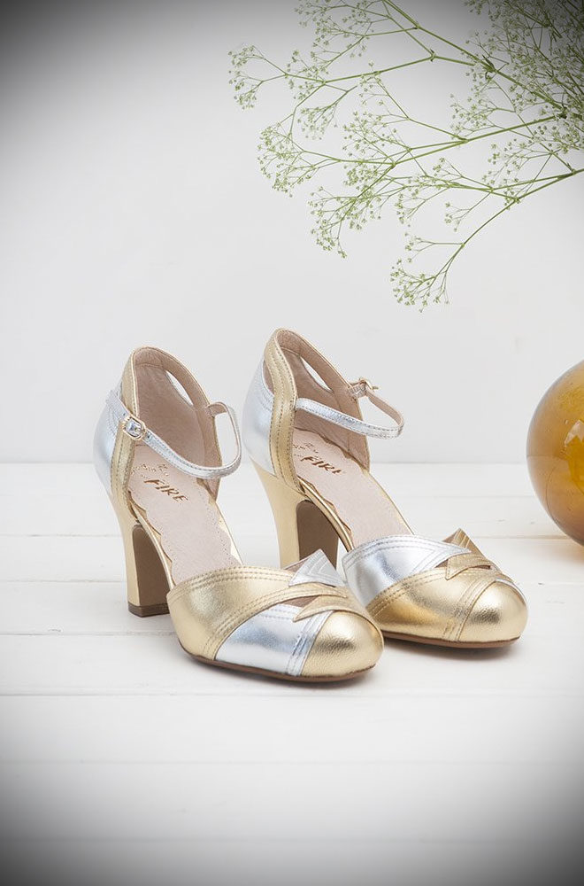 The Miss L Fire Gold and Pewter Grace Shoes are beautiful vintage inspired heels. Made in stunning metallic leather these fantastic 40s shoes have are just charming. These two-tone leather court shoes feature an adjustable ankle strap & diamond-shaped cut-out details on the vamp. Available now at DeadlyistheFemale.com