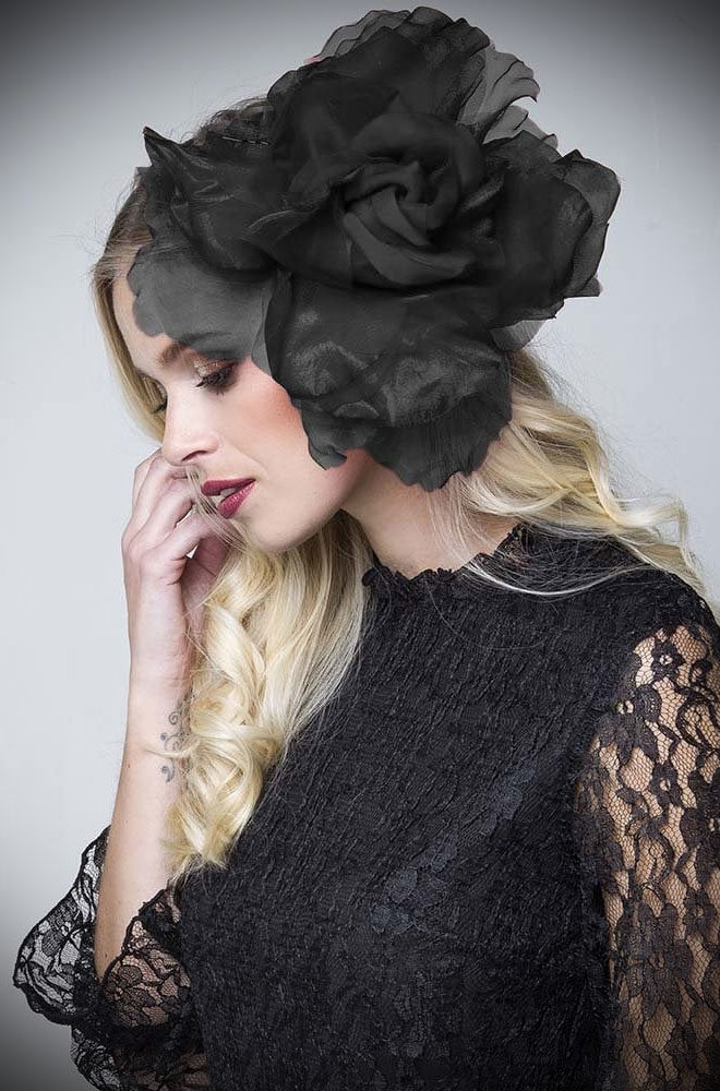 The Statement Black Rose Fascinator is sure to turn heads! We absolutely adore this oversized black floral hair accessory/brooch.