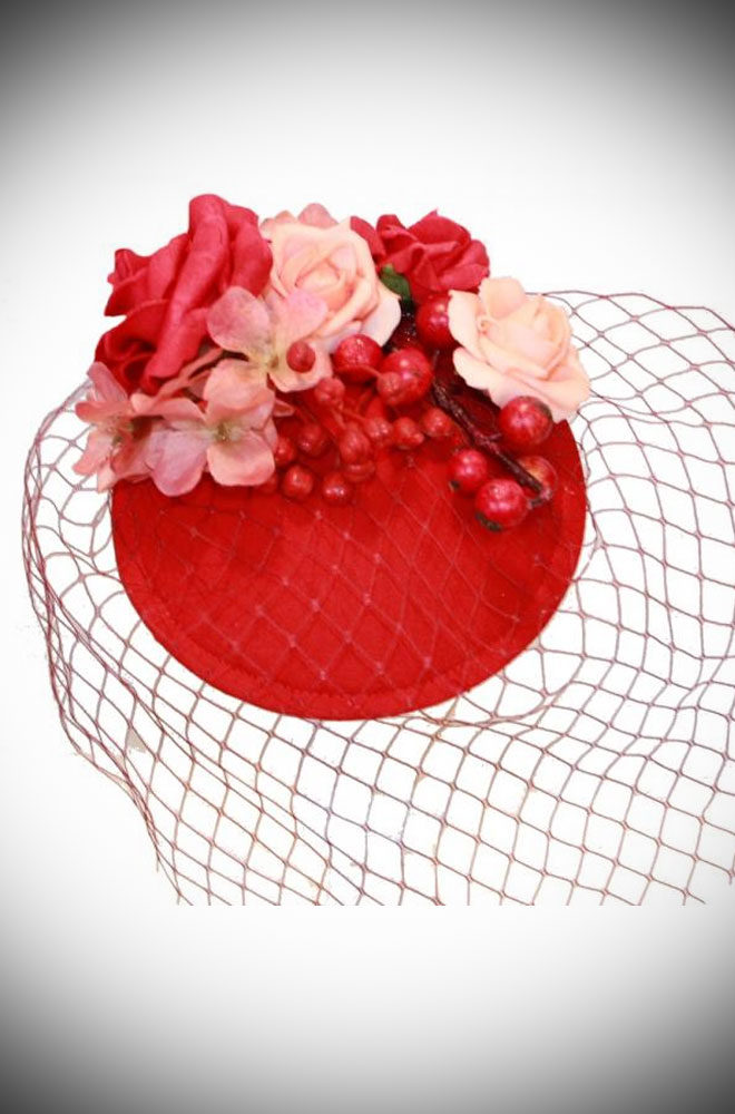 The Camille Red Rose Fascinator is adorned with a delicate ensemble of roses and small berries in harmonious hues of red.