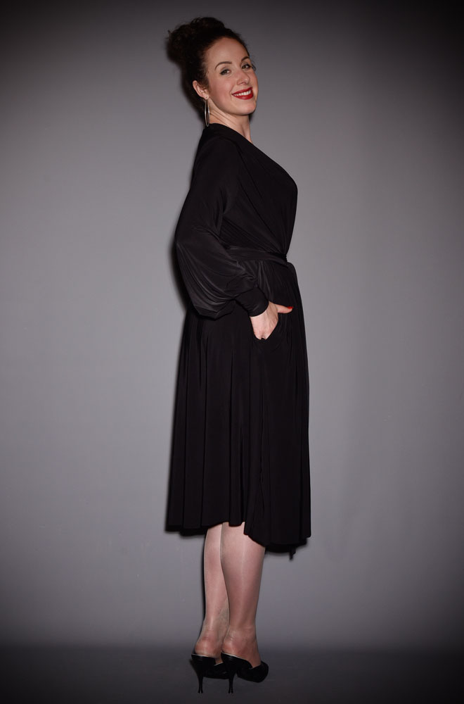 The Black Claudia Dress is a draped jersey dress with sash waist & bishop sleeves. A signature piece by Alexandra King for Deadly is the Female.