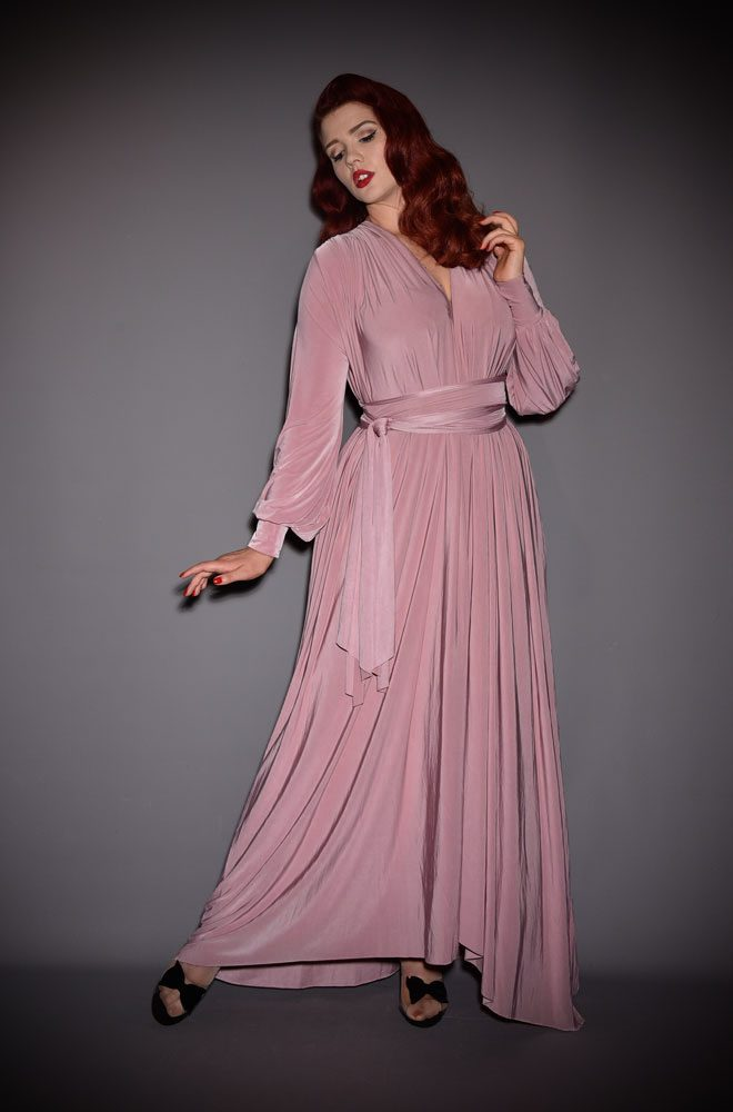 The Dusty Rose Claudia Gown is a draped jersey evening dress with sash waist & bishop sleeves. A signature piece by Alexandra King for Deadly is the Female.