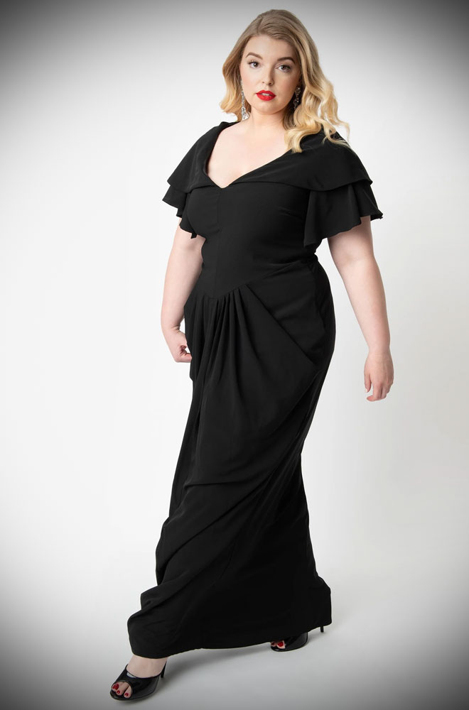 The 1940s Style Zhora Hooded Gown is a breathtaking gown which is guaranteed to turn heads. Designed exclusively by Micheline Pitt for Unique Vintage. We are extremely excited to be an official UK stockist. The 1940s Style Zhora Hooded Gown is an elegant 1940s style evening gown. This gown is a stunning black maxi dress in a rippling Grecian style for an ornate and refined silhouette. The sultry bodice drops into a Basque waistline, slightly lower than your natural waist. The gathers at the hip also evoke a classic 1940s style. This silhouette is framed by graceful angel sleeves that flutter to the elbow. A beautifully draped hood lends drama when worn up and also looks like an elegant cowl when worn down. The gathered front drops into a Grecian column style, sweeping to the floor with effortless grace. The dress is finished with a hidden side zip. This dress is a true scene-stealer!  95% Polyester 5% Spandex Dry Clean Only Side zip, lined Attached hood Material has no stretch Finally, the 1940s Style Zhora Hooded Gown is made by Unique Vintage - they have recently changed up their size chart so we strongly recommend that you check your measurements. We have changed the label sizes to the best fit in UK sizes but they label size and US size are shown at the end of the size chart. See our quick video on measuring yourself here.