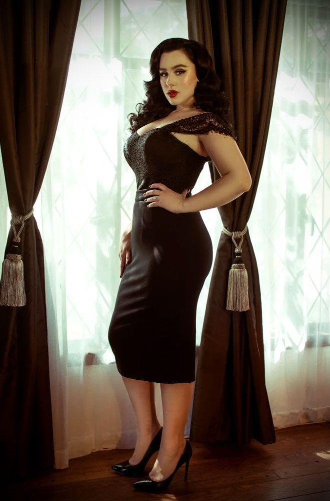 The Black Vamp Pencil Skirt, designed for Femme Fatales who can't live without a little drama! The Black Vamp Pencil Skirt has the same great design and fit as the popular Vixen pencil skirt, but this version is in a heavy stretch Ponte. This will give girls with extreme waist to hip measurements a figure-flattering and form-fitting pencil skirt. This skirt is also super comfortable! It features a back zip, fused waistband, a soft lining and back slit for easy movement. This is a limited-edition colourway. The classic black is timeless and can be paired with a variety of colours and prints to ensure you look glamorous all year round! Made in Hollywood, California. Deadly is the Female are the official UK and European stockists of La Femme En Noir. Specialising in dark and elegant designs for the glamorously gothic, La Femme En Noir is made in LA by designers Lynh Haaga & Micheline Pitt. With a cult following and new collections every season, you'll soon see what all the fuss is about!