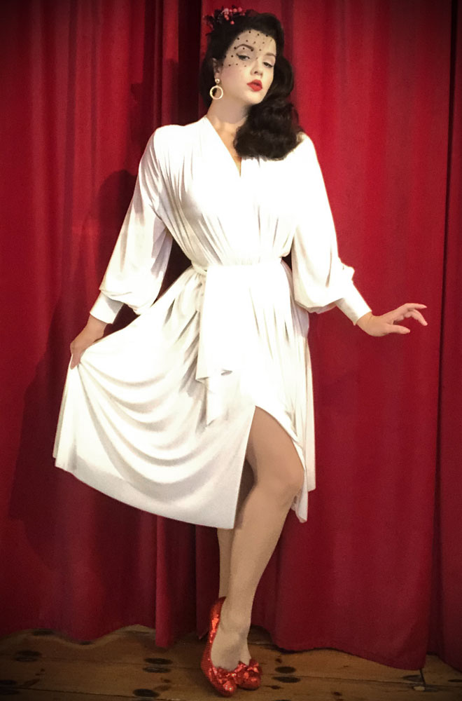 The Ivory Claudia Dress is a draped jersey dress with sash waist & bishop sleeves. A signature piece by Alexandra King for Deadly is the Female.